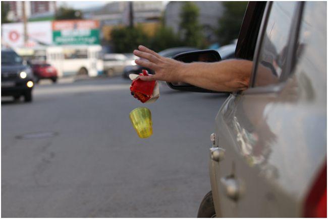 человек, выбрасывающий мусор из машины