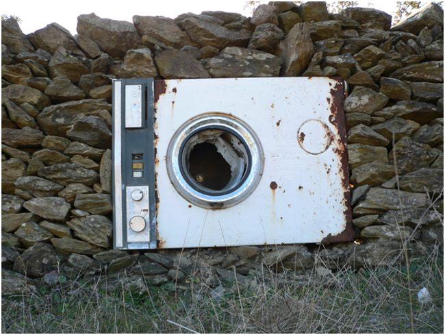 ржавая стиральная машина в камнях