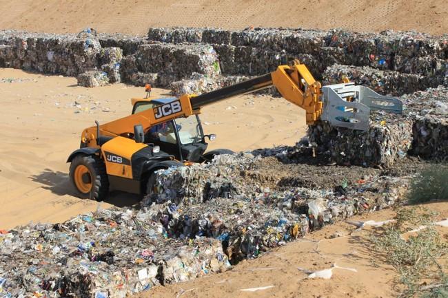 экскаватор грузит мусор